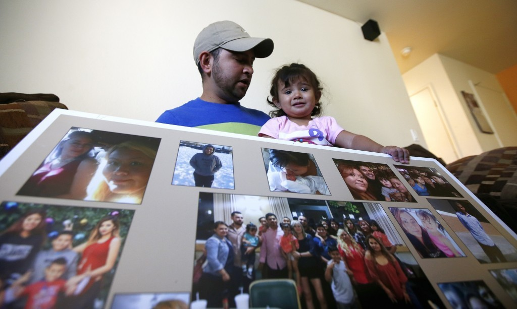 Cesar Garcia, left, talks with his 1-year-old daughter Marina, right, as they look at photographs of family members, many of whom were killed in the f...