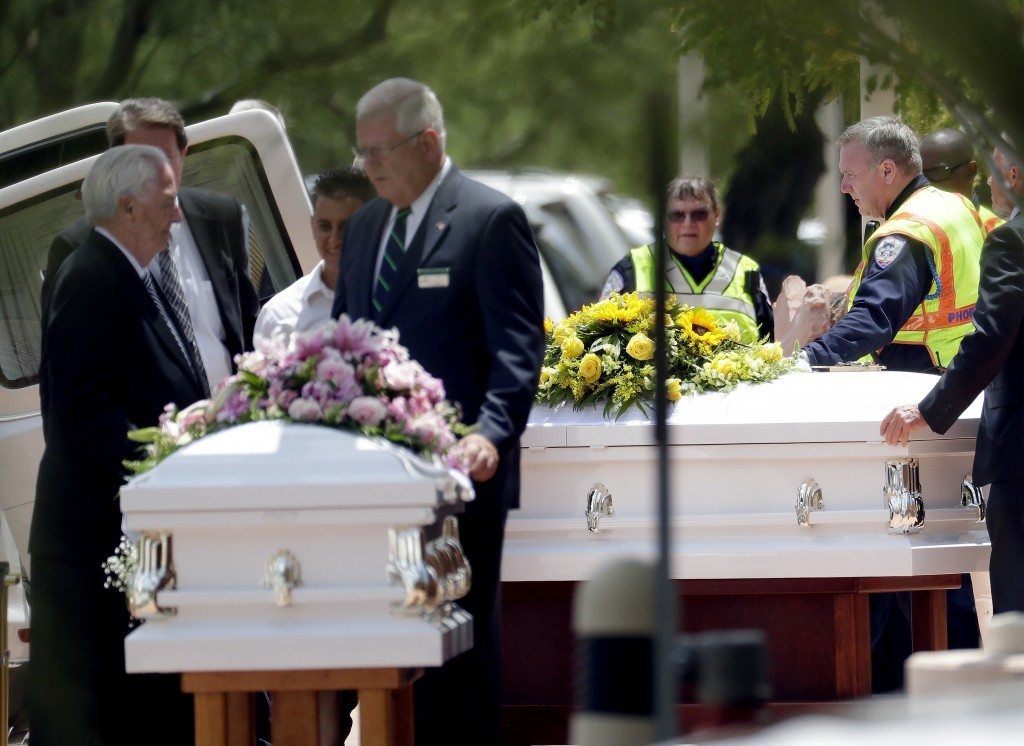 FILE - In this July 25, 2017 file photo, the caskets of family members who were killed in a flash flood are loaded into hearses outside St. Patrick Ca...