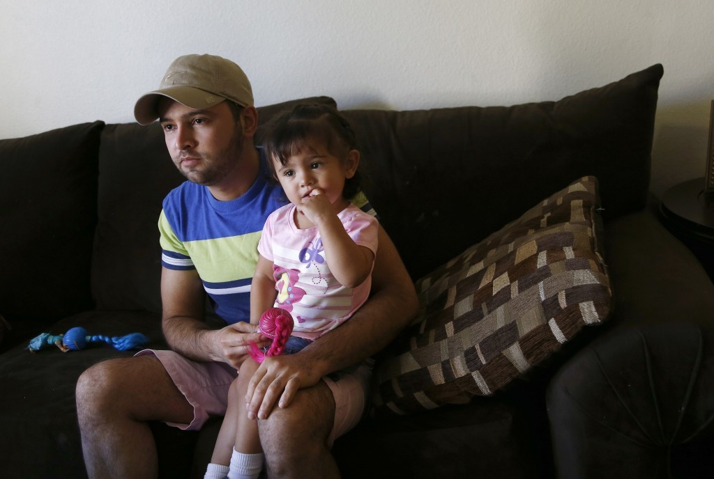 Cesar Garcia, left, sits with 1-year-old daughter Marina, as talks about how he and other family members, including Marina, survived the Payson, Ariz....