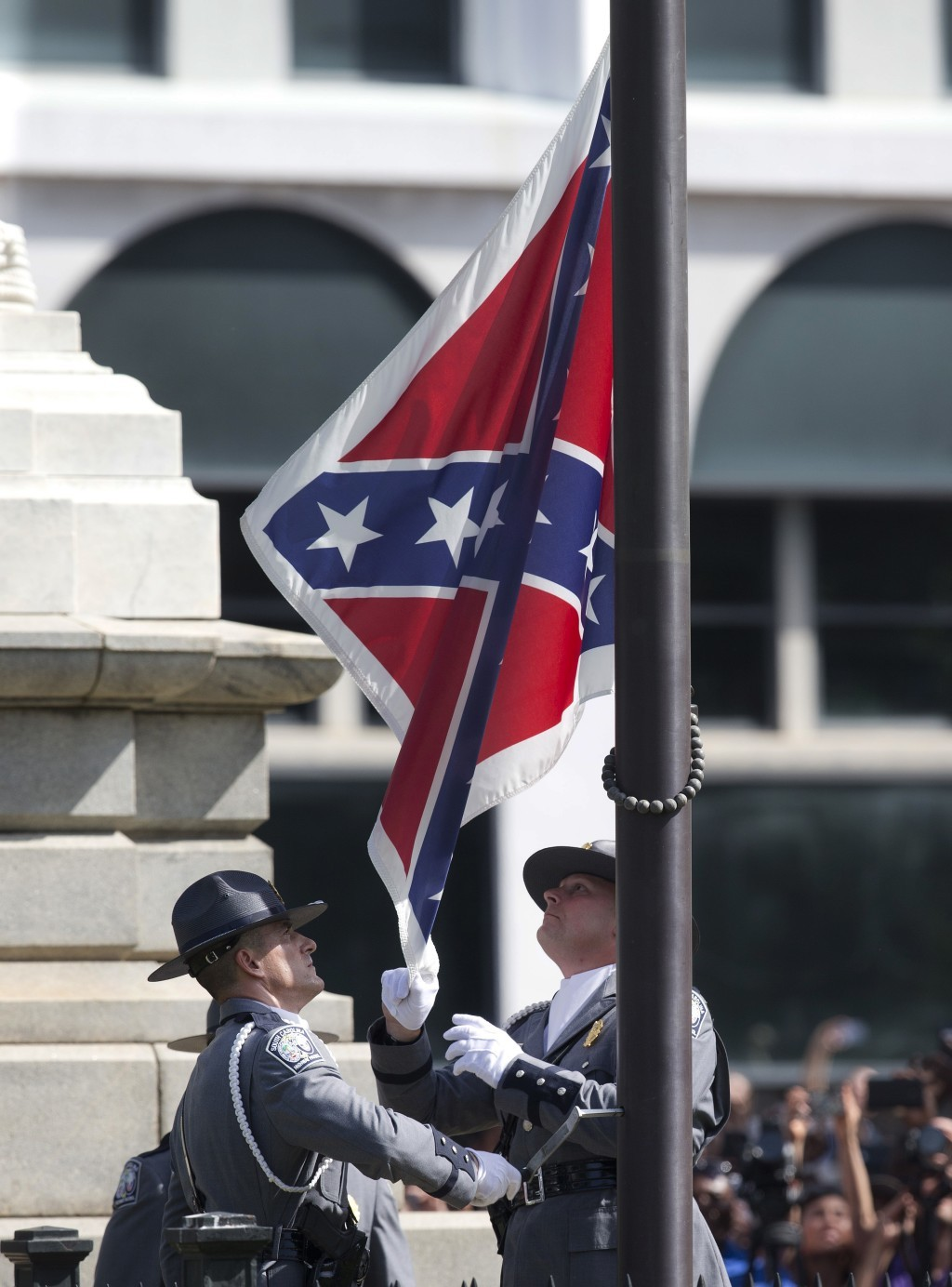 FILE - In this July 10, 2015 file photo, an honor guard from the South Carolina Highway patrol removes the Confederate battle flag from the Capitol gr...