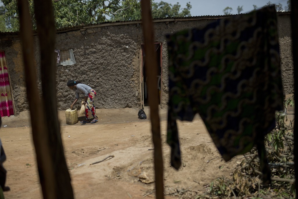 In this photo taken Aug. 10, 2016, Bora, 22, prepares do fetch water in the Congo Ituri province capital Bunia. Bora said she was just 11 when she bec...