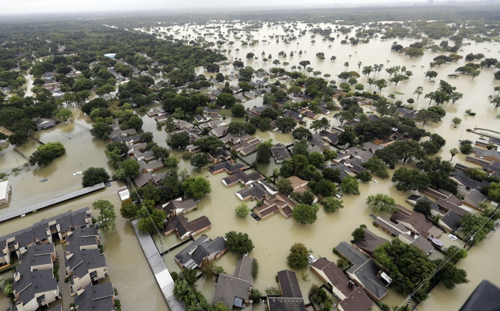 FILE - In this Aug. 29, 2017, file photo, water from Addicks Reservoir flows into neighborhoods from floodwaters brought on by Tropical Storm Harvey i...