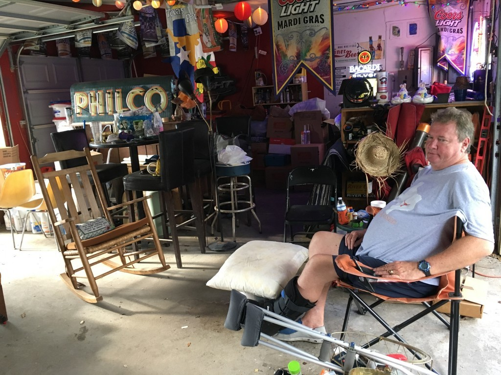 In this Sept. 20, 2017 photo, Houston resident Bob Cantrell sits in his garage surrounded by the few pieces of furniture and personal items he was abl...