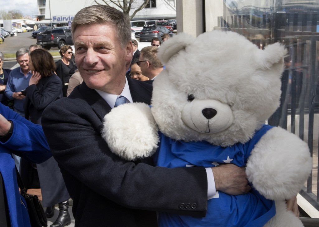 New Zealand Prime Minister Bill English embraces a National Party mascot while on the campaign trail in Cambridge, New Zealand, Friday, Sept. 22, 2017...