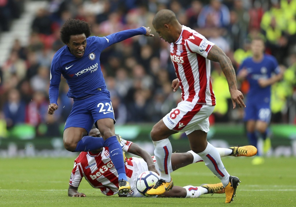 Chelsea's Willian, left, and Stoke City's Glen Johnson battle for the ball during the English Premier League soccer match between Stoke City and Chels...