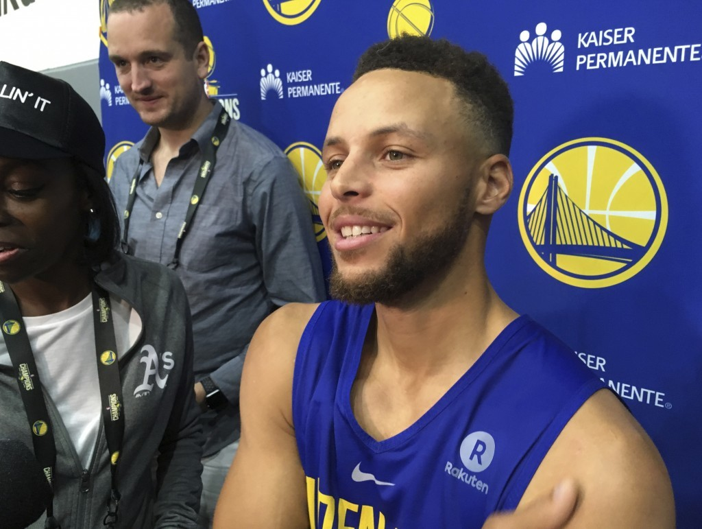 Golden State Warriors Stephen Curry takes questions from the media after NBA basketball practice in Oakland, Calif., Saturday, Sept. 23, 2017. Preside...