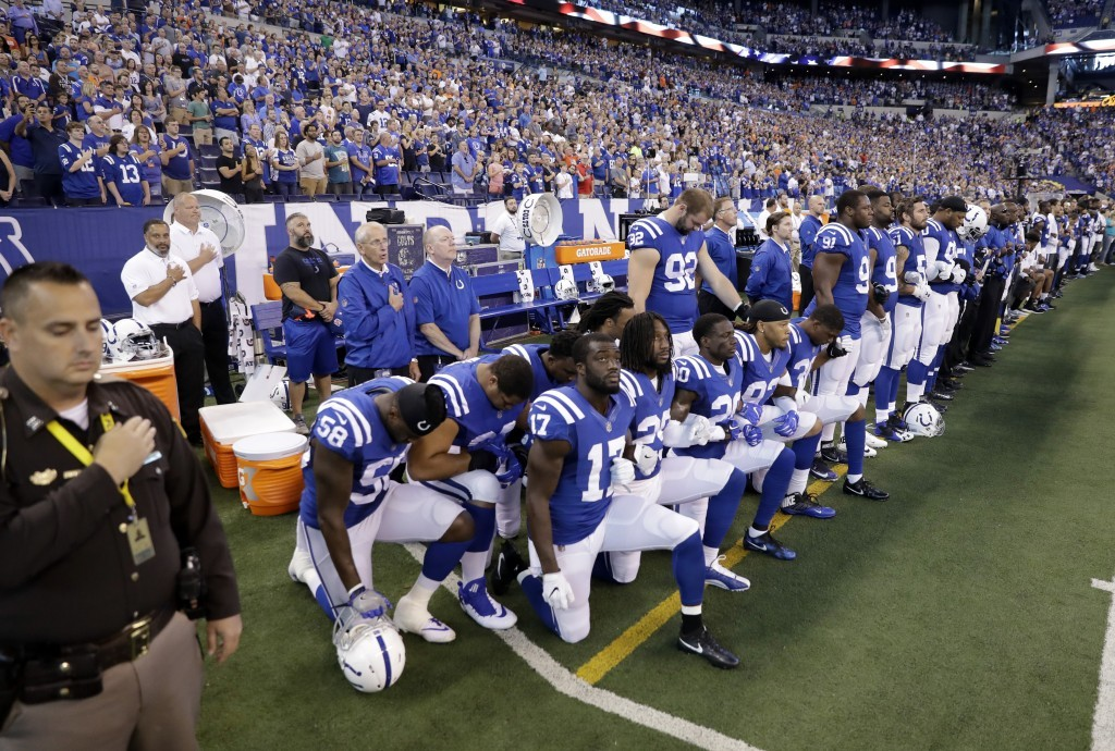 Members of the Indianapolis Colts take a knee during the nation anthem before an NFL football game against the Cleveland Browns in Indianapolis, Sunda...