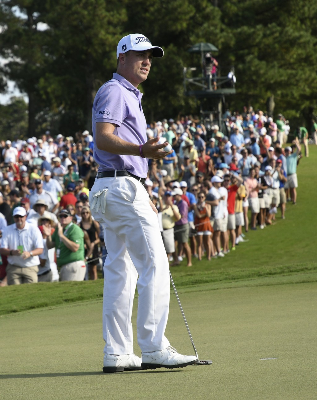 Justin Thomas picks up his ball after scoring a birdie on hole seventeen during the final round of the Tour Championship golf tournament at East Lake ...