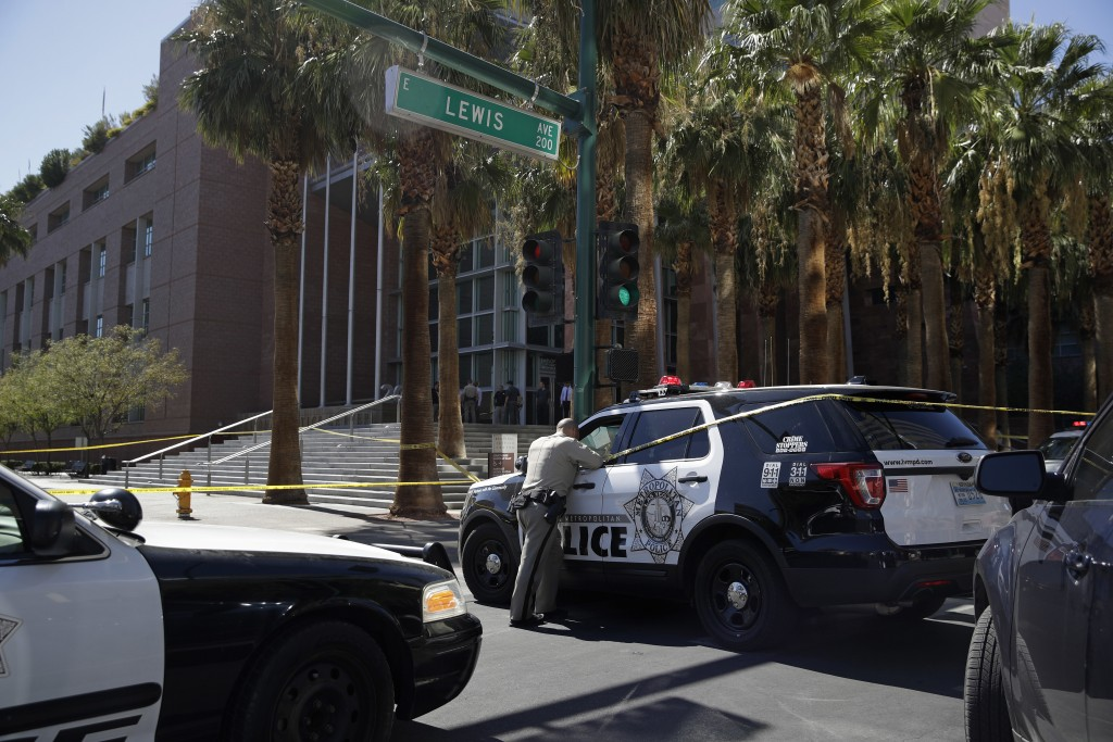 Police investigate a crime scene in front of the Regional Justice Center court house, Monday, Sept. 25, 2017, in Las Vegas. Police say a woman was str...