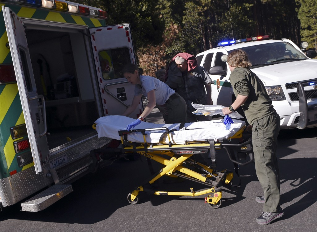 Emergency personnel prepare to care for an elderly man, center background, who was injured after a new rock fall on El Capitan occurred Thursday after...