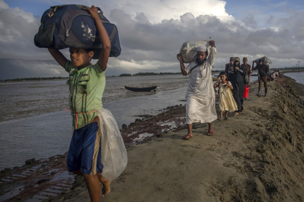 FILE - In this Thursday, Sept. 28, 2017, file photo, newly arrived Rohingya Muslims, who crossed over from Myanmar into Bangladesh, walk with their be...