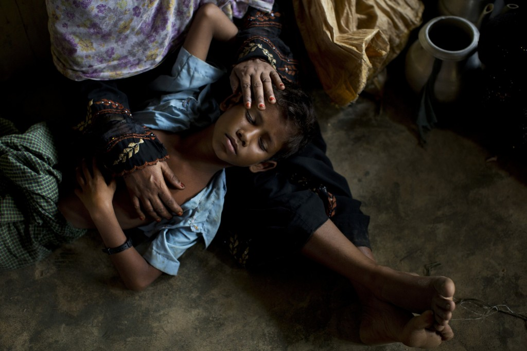 FILE - In this Thursday, Sept. 7, 2017, file photo, Rohingya woman comforts her exhausted son as they take shelter inside a school after having just a...