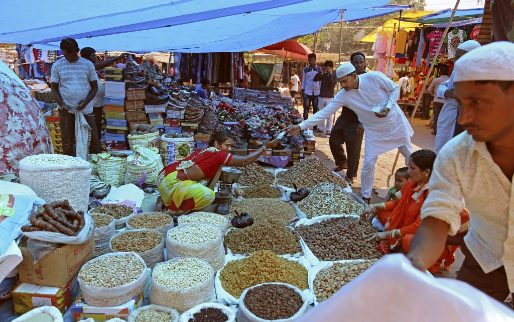 FILE - In this June 16, 2017, file photo, Indians buy dry fruits from a roadside vendor at a market in New Delhi, India. Three years later Prime Minis...