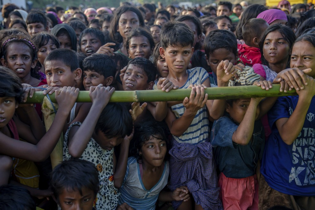 FILE - In this Monday, Sept. 25, 2017, file photo, Rohingya Muslim children, who crossed over from Myanmar into Bangladesh, wait to receive aid during...