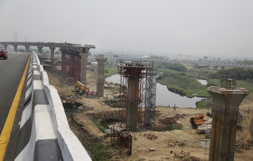 FILE - In this June 1, 2017, file photo, an Indian man walks beneath an under construction flyover in New Delhi, India. Three years later Prime Minist...