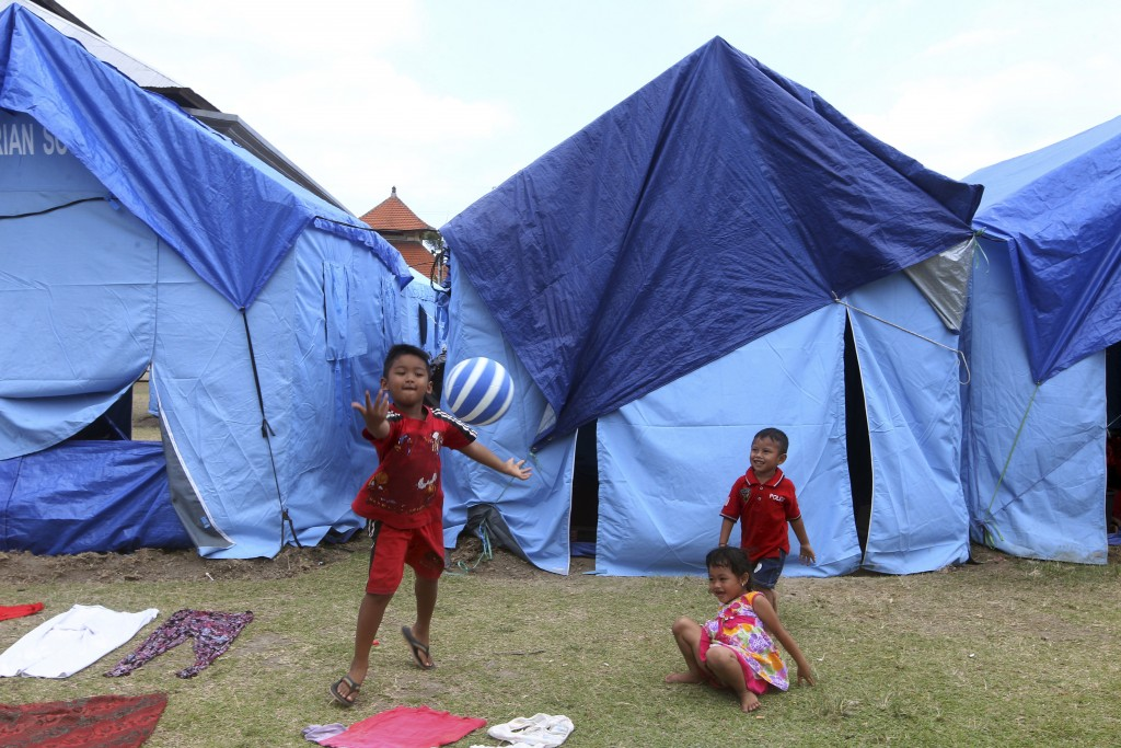 Children play outside they temporary shelter at an evacuee camp outside of the Mount Agung volcano in Klungkung, Bali, Indonesia, Saturday, Sept. 30,