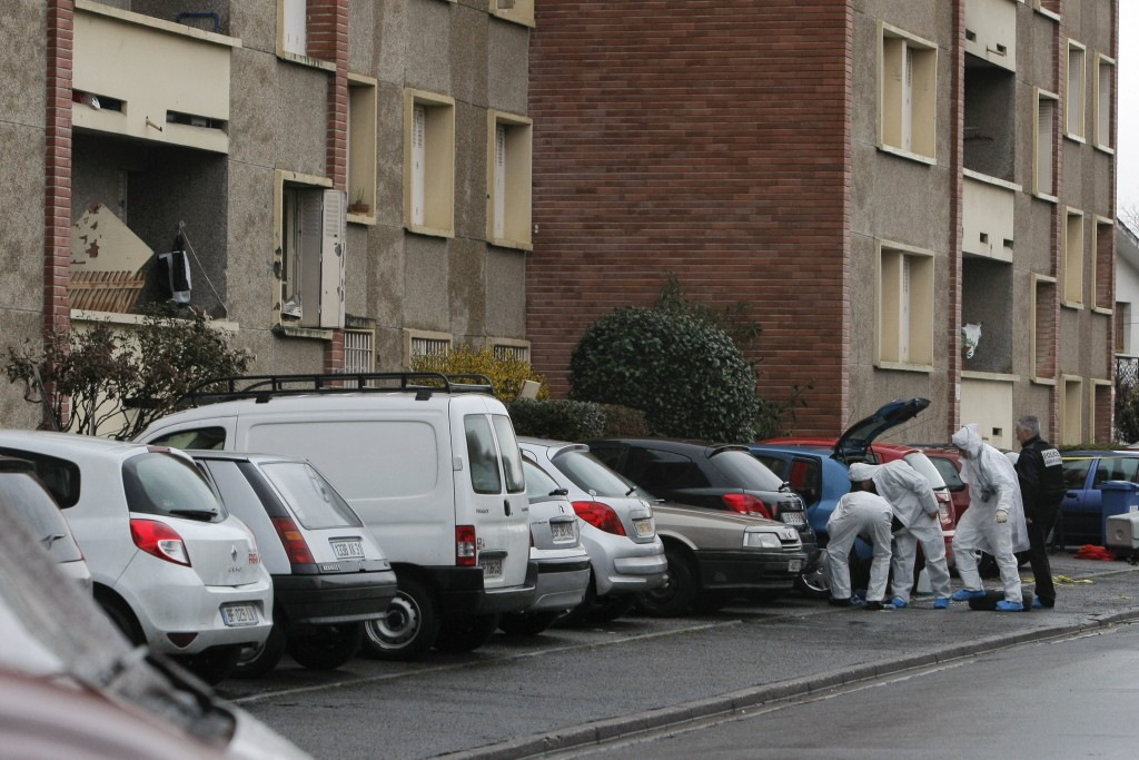 FILE - In this file photo dated Thursday, March 22, 2012, French police officers work outside the apartment of Mohamed Merah, left, in Toulouse, Franc...