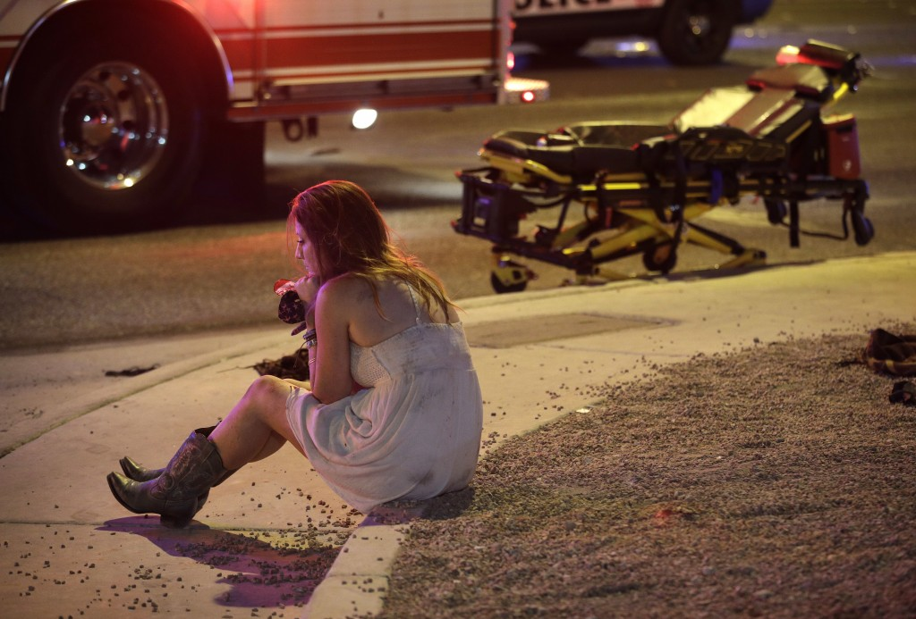 A woman sits on a curb at the scene of a shooting outside of a music festival along the Las Vegas Strip, Monday, Oct. 2, 2017, in Las Vegas. Multiple ...