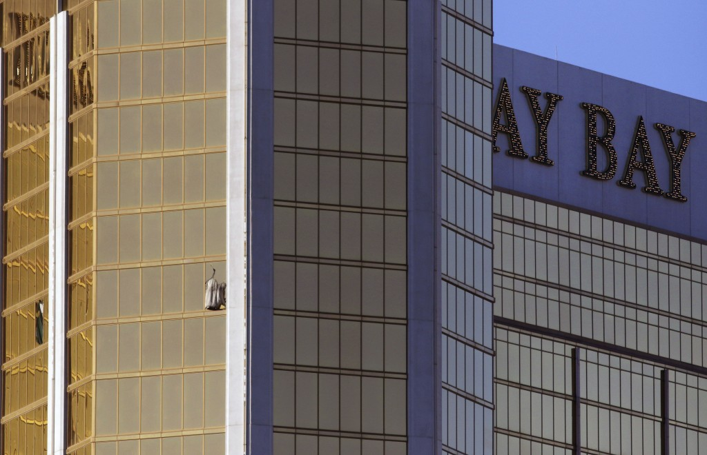 Drapes billow out of a broken window at the Mandalay Bay resort and casino Monday, Oct. 2, 2017, on the Las Vegas Strip following a deadly shooting at...
