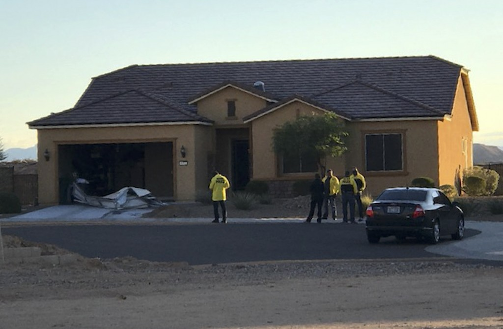 In this photo provided by the Mesquite, Nev., Police Department, police personnel stand outside the home of Stephen Paddock on Monday, Oct. 2, 2017, i...