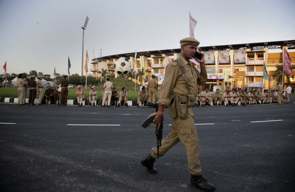 A security officer walks past others outside Indira Gandhi Athletic Stadium, one of the venues for the FIFA U-17 World Cup football, in Gauhati, India...