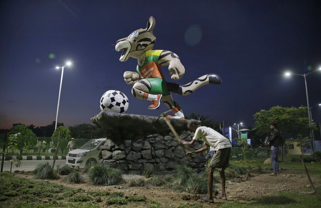 An Indian laborer works beside the FIFA U-17 World Cup mascot outside Indira Gandhi Athletic Stadium, one of the venues for the championship, in Gauha...