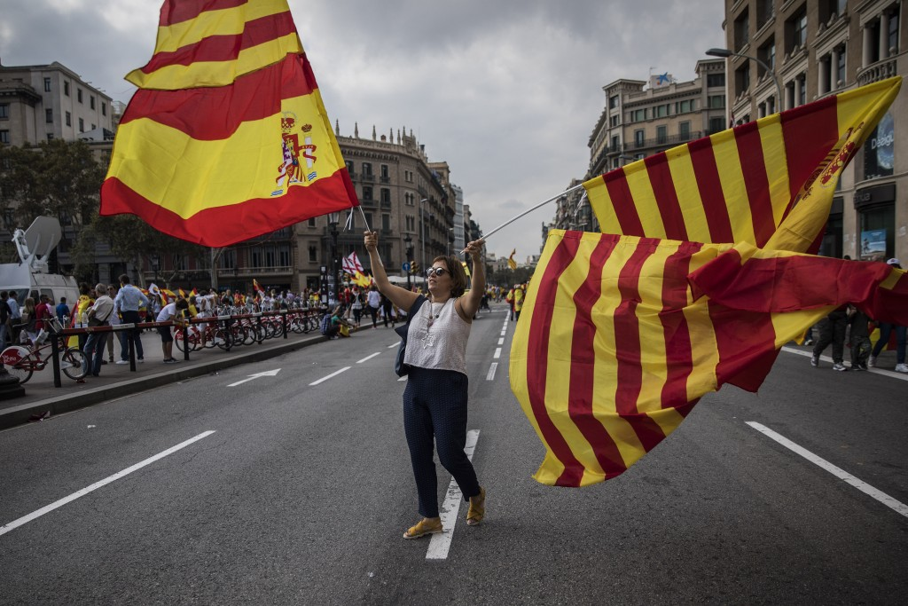"""A woman waves flags of Catalonia and Spain as people celebrate a holiday known as """"Dia de la Hispanidad"""" or Spain's National Day in Barcelona, Spain,"""