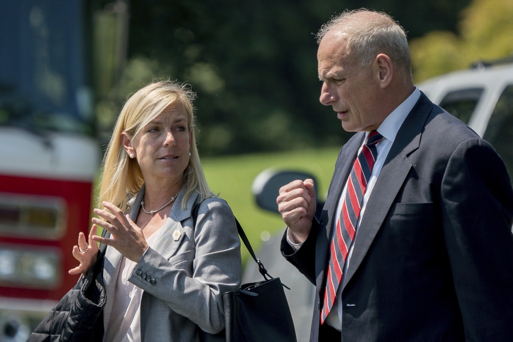 In this Aug. 22, 2017 photo, White House Chief of Staff John Kelly and Deputy Chief of Staff Kirstjen Nielsen speak together as they walk across the S