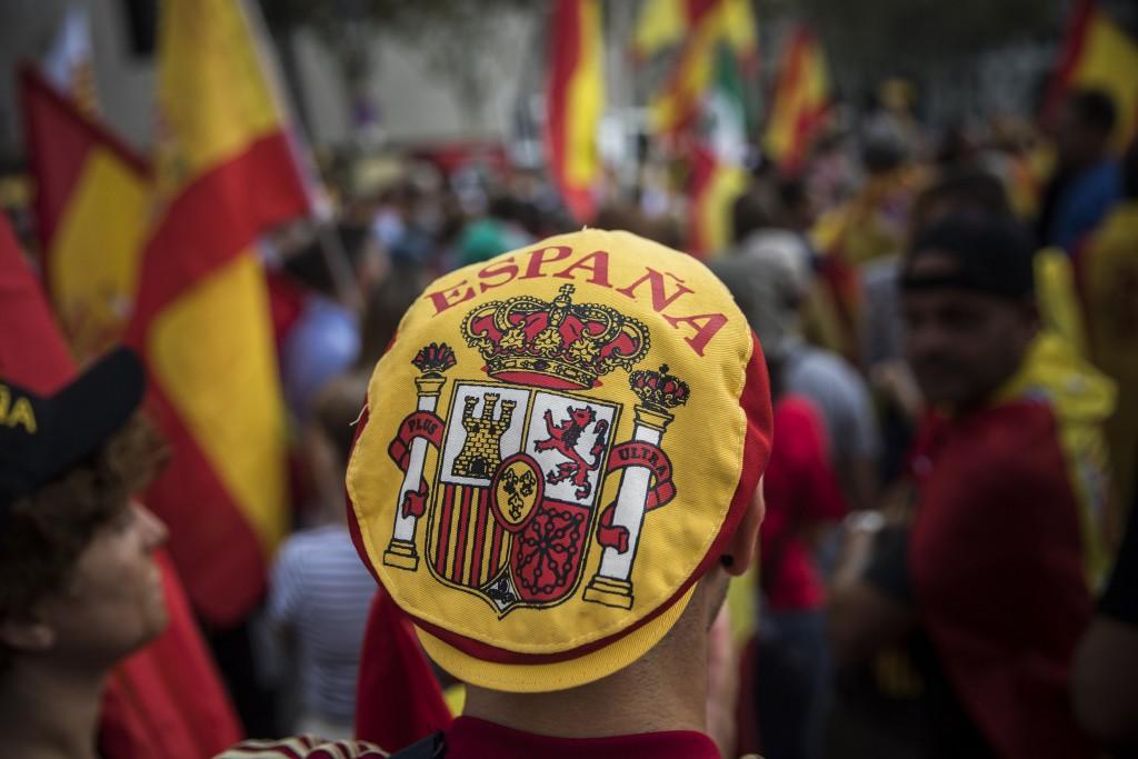 """A man wears a hat with the coat of arms of the Spanish flag while people celebrate a holiday known as """"Dia de la Hispanidad"""" or Spain's National Day i"""
