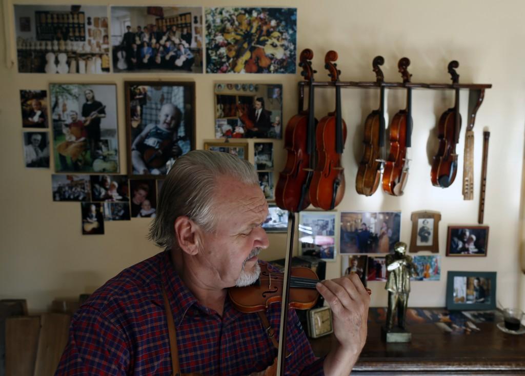 Violin maker Jan Nemcek plays small violin, in the northern Serbian village of Kovacica, Wednesday, Oct. 4, 2017. Nemcek picks up his own wood from th