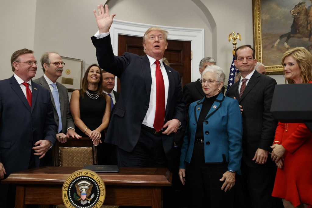 President Donald Trump waves after signing an executive order on health care in the Roosevelt Room of the White House, Thursday, Oct. 12, 2017, in Was...