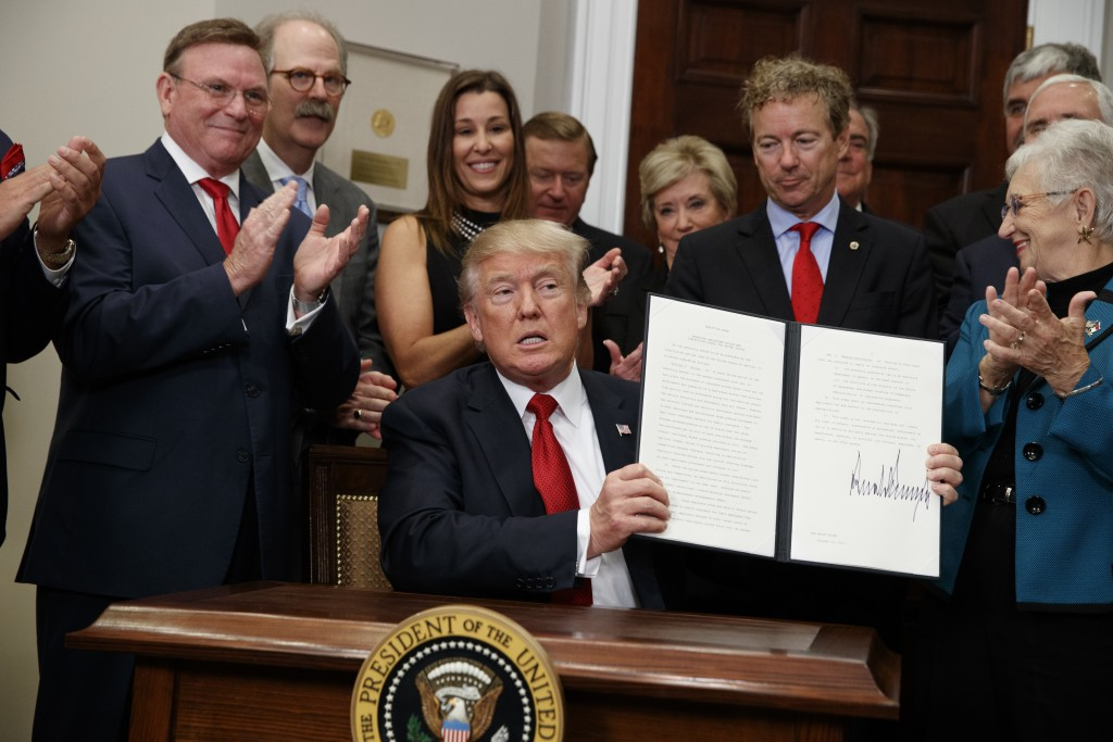 President Donald Trump shows an executive order on health care that he signed in the Roosevelt Room of the White House, Thursday, Oct. 12, 2017, in Wa
