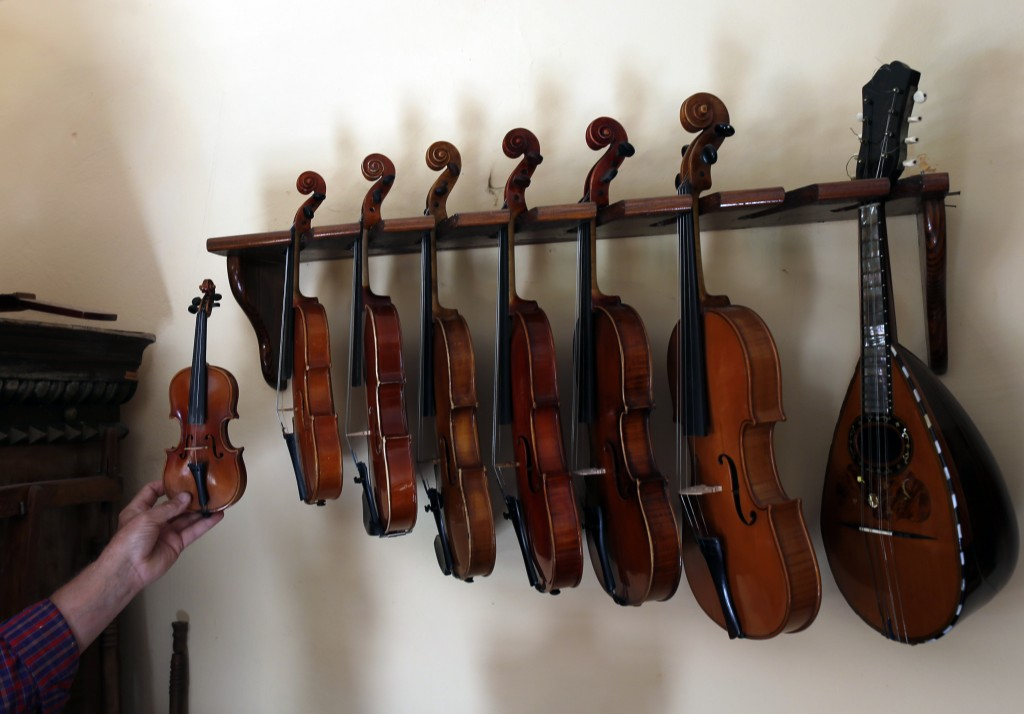 Violin maker Jan Nemcek shows the smallest violin comparing it with bigger violins, in the northern Serbian village of Kovacica, Wednesday, Oct. 4, 20