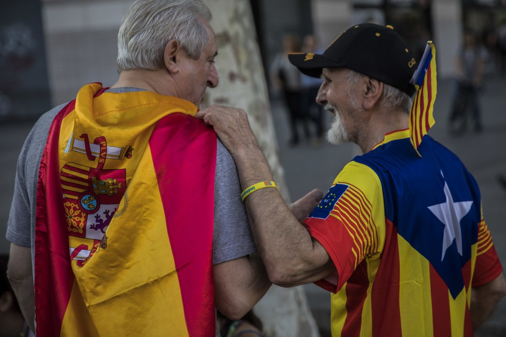 Two men, one wearing a Spanish flag, left, and the other wearing an estelada' or independence flag, talk during the celebration of a holiday known as