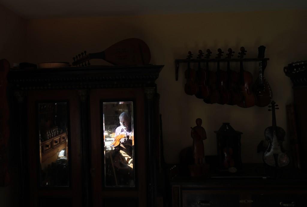 A reflection of violin maker Jan Nemcek polishing a violin seen in a mirror, in the northern Serbian village of Kovacica, Wednesday, Oct. 4, 2017.  Ne