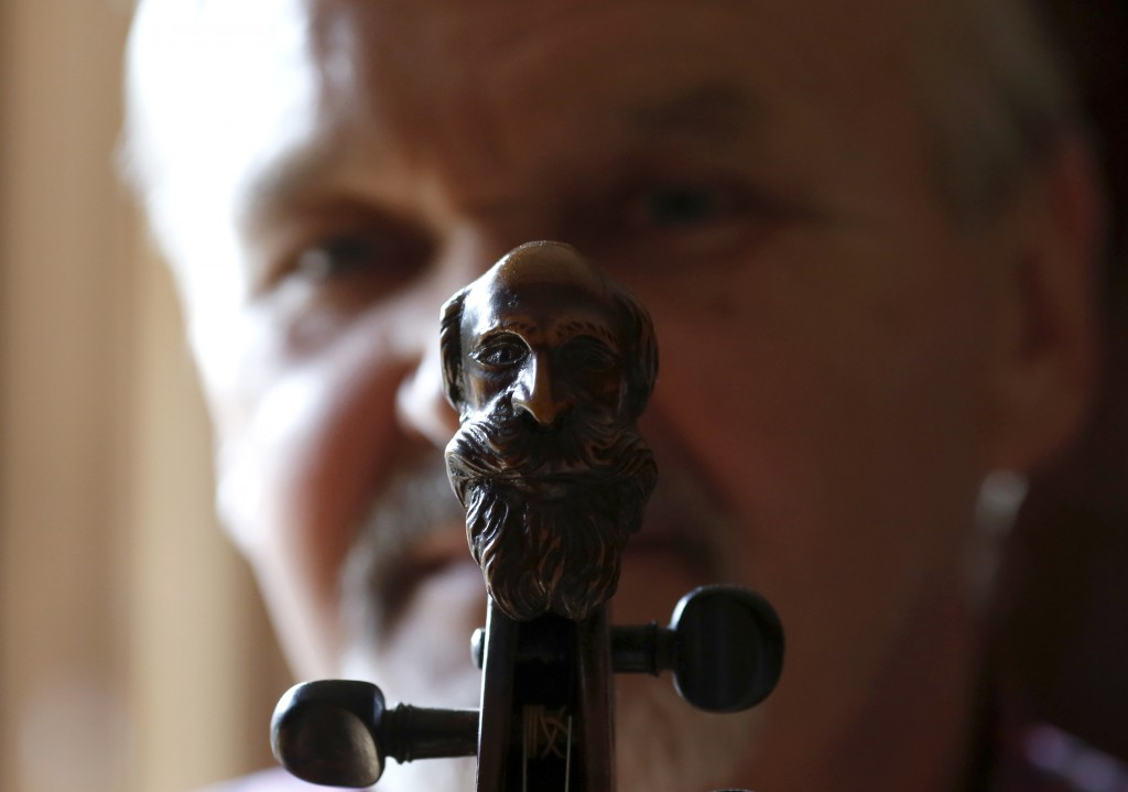 Violin maker Jan Nemcek poses holding his favourite repaired 500 years old violin, in the northern Serbian village of Kovacica, Wednesday, Oct. 4, 201