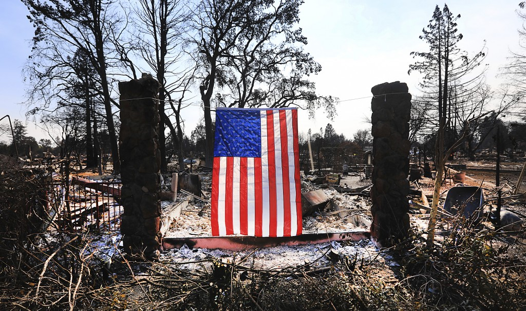 On Willowview Court in Santa Rosa, Calif., a homeowner displays an American flag amidst the destruction from a wildfire, Thursday Oct. 12, 2017. Since