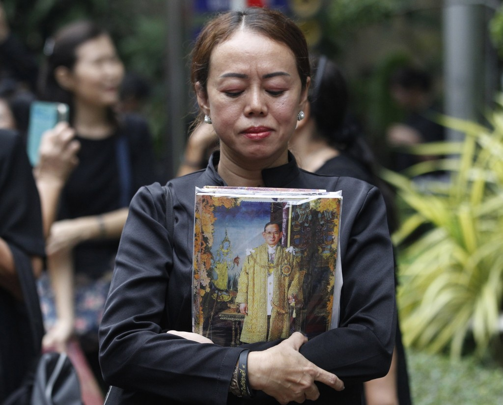 Thai mourner holds a portrait of the late Thai King Bhumibol Adulyadej at Siriraj Hospital where he died in Bangkok, Thailand, Friday, Oct. 13, 2017.