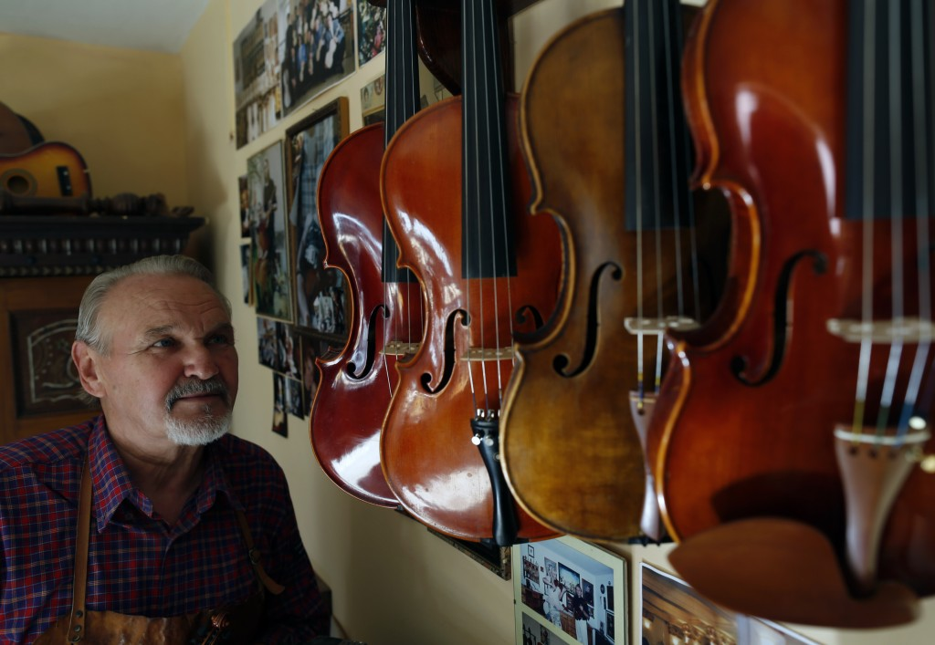 Violin maker Jan Nemcek poses by different violins hanging on the wall, in the northern Serbian village of Kovacica, Wednesday, Oct. 4, 2017. Nemcek i