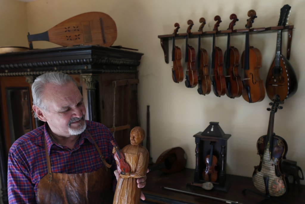 Violin maker Jan Nemcek shows a wooden statue of him, made by his wife, in the northern Serbian village of Kovacica, Wednesday, Oct. 4, 2017.  Nemcek