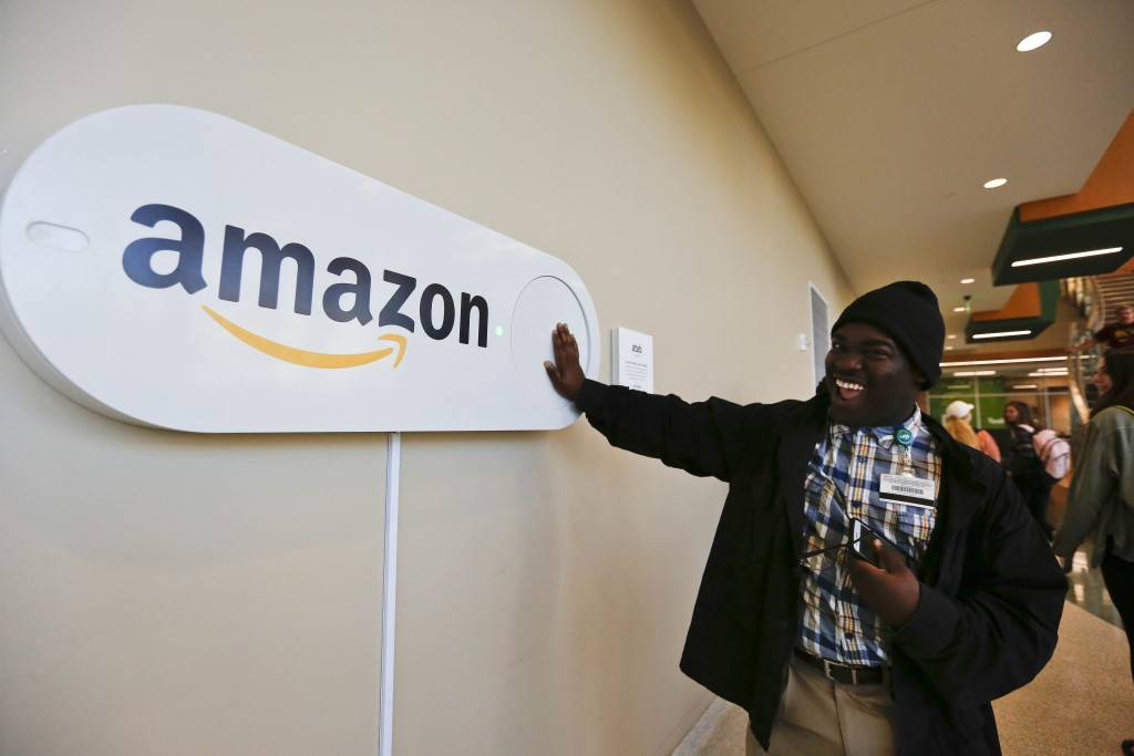 FILE - In this Monday, Oct. 16, 2017, file photo, Zavian Tate, a student at the University of Alabama at Birmingham, pushes a large Amazon Dash button...