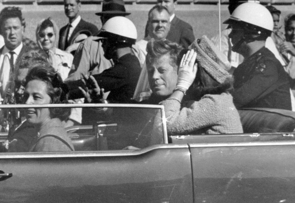 FILE - In this Nov. 22, 1963 file photo, President John F. Kennedy waves from his car in a motorcade in Dallas. Riding with Kennedy are First Lady Jac...