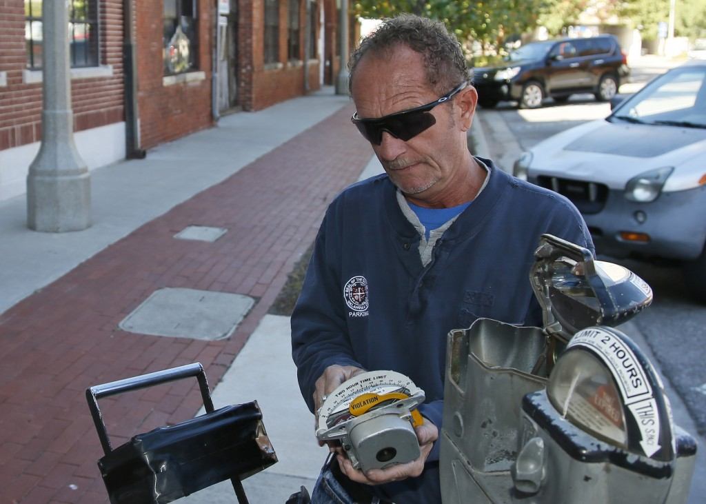 In this Wednesday, Oct. 11, 2017 photo, Wade Beal, parking meter technician, inspects a parking meter in Oklahoma City. Oklahoma City, where the parki...