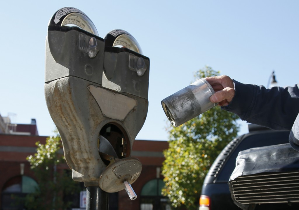 In this Wednesday, Oct. 11, 2017 photo, Wade Beal, parking meter technician, removes a container of coins from a parking meter in to collection can in...