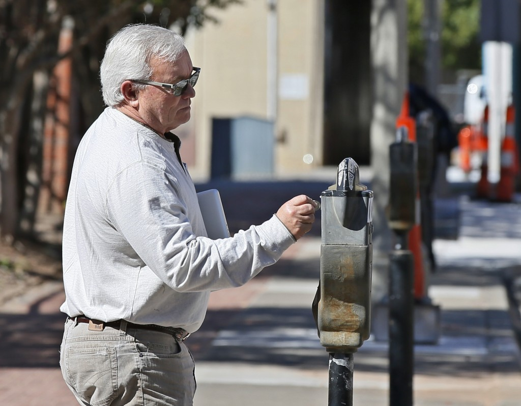 In this Wednesday, Oct. 11, 2017 photo, Mickey Thompson puts coins into a parking meter in Oklahoma City.   The city where parking meters were born sa...