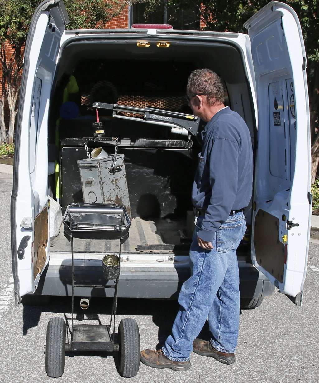 In this Wednesday, Oct. 11, 2017 photo, Wade Beal, parking meter technician, uses a small crane in the back of his vehicle to remove the can which hol...