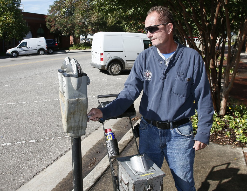In this Wednesday, Oct. 11, 2017 photo, Wade Beal, parking meter technician, uses a key to open a parking meter and remove the coins in Oklahoma City....