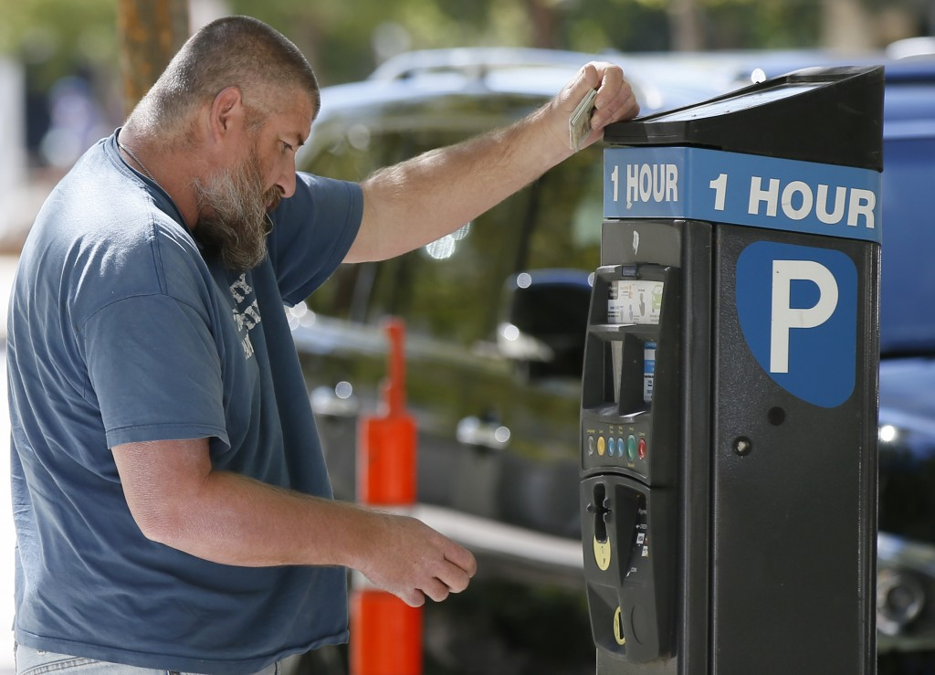 In this Wednesday, Oct. 11, 2017 photo, Will Cross, reads the directions on a parking pay station in Oklahoma City. Oklahoma City, where the parking m...