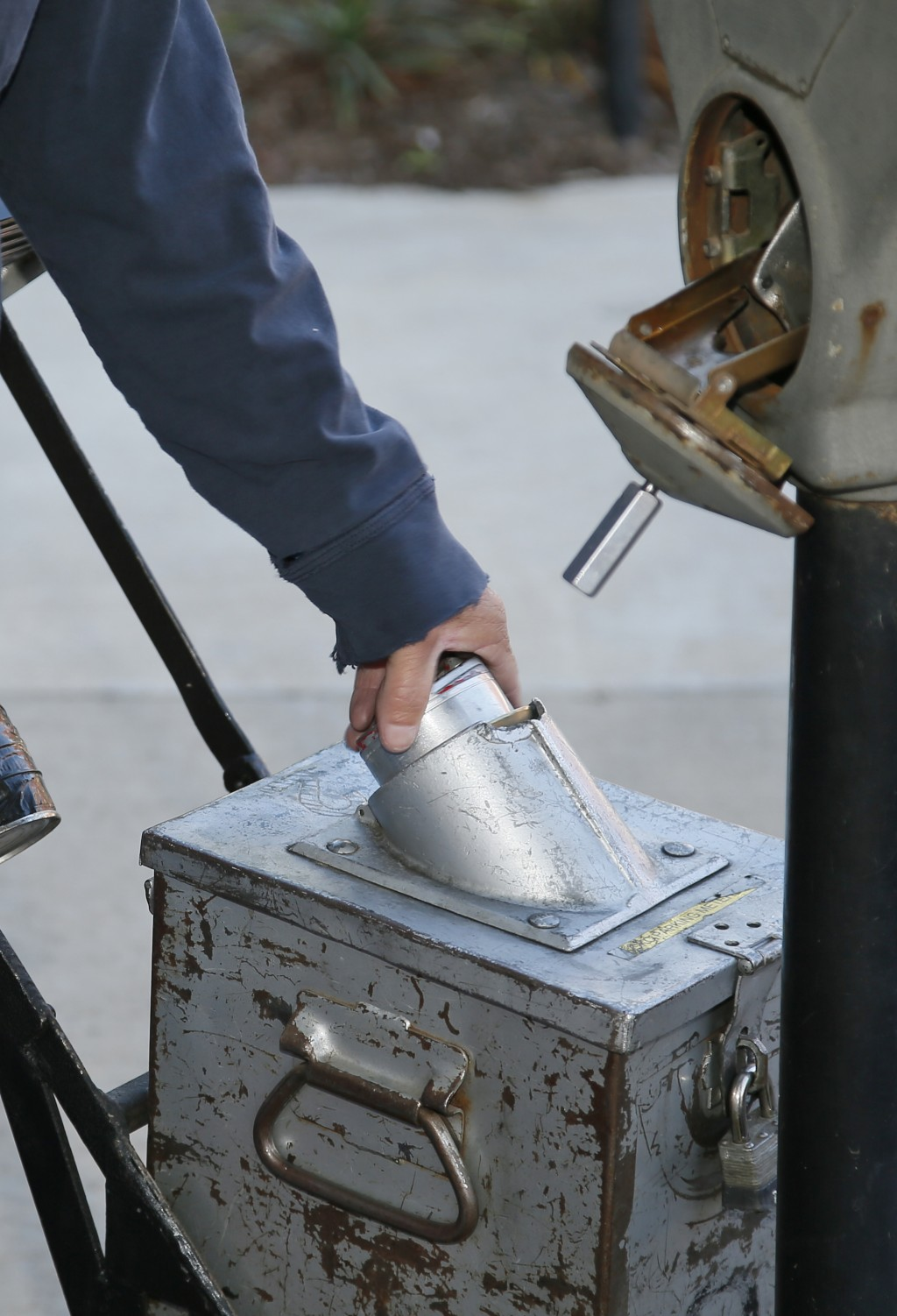 In this Wednesday, Oct. 11, 2017 photo, Wade Beal, parking meter technician, empties coins from a parking meter into a locked collection can in Oklaho...