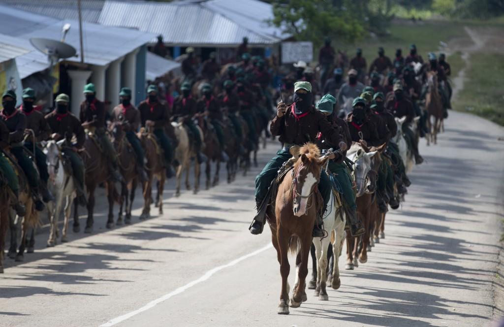 In this Saturday, Oct. 14, 2017 photo, members of the Zapatista National Liberation Army (EZLN) arrive on horseback to escort Maria de Jesus Patricio,...